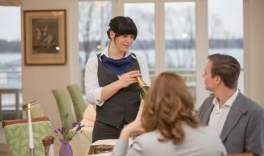 Service-Mitarbeiterin empfiehlt Restaurant-Gästen ein Champagner.
