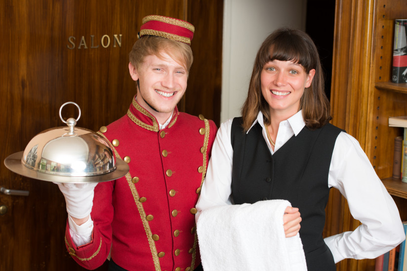 zwei Hotel-Auszubildende in typischer Uniform