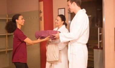 Spa-Mitarbeiterin reicht Gästen frische Handtücher