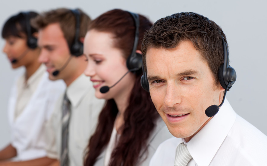 Attractive man working with his team in a call center with a headset on